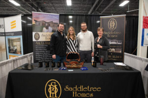 4 people standing behind saddletree homes booth