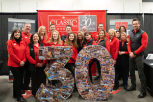 18 members of the classic homes team standing for a 30 year anniversary picture.
