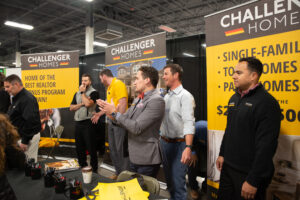 six people standing behind a challenger homes booth at a convention.