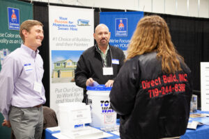 three people talking about builder products at an event