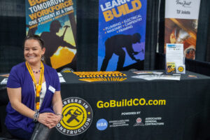 One person smiling in front of their booth at an event