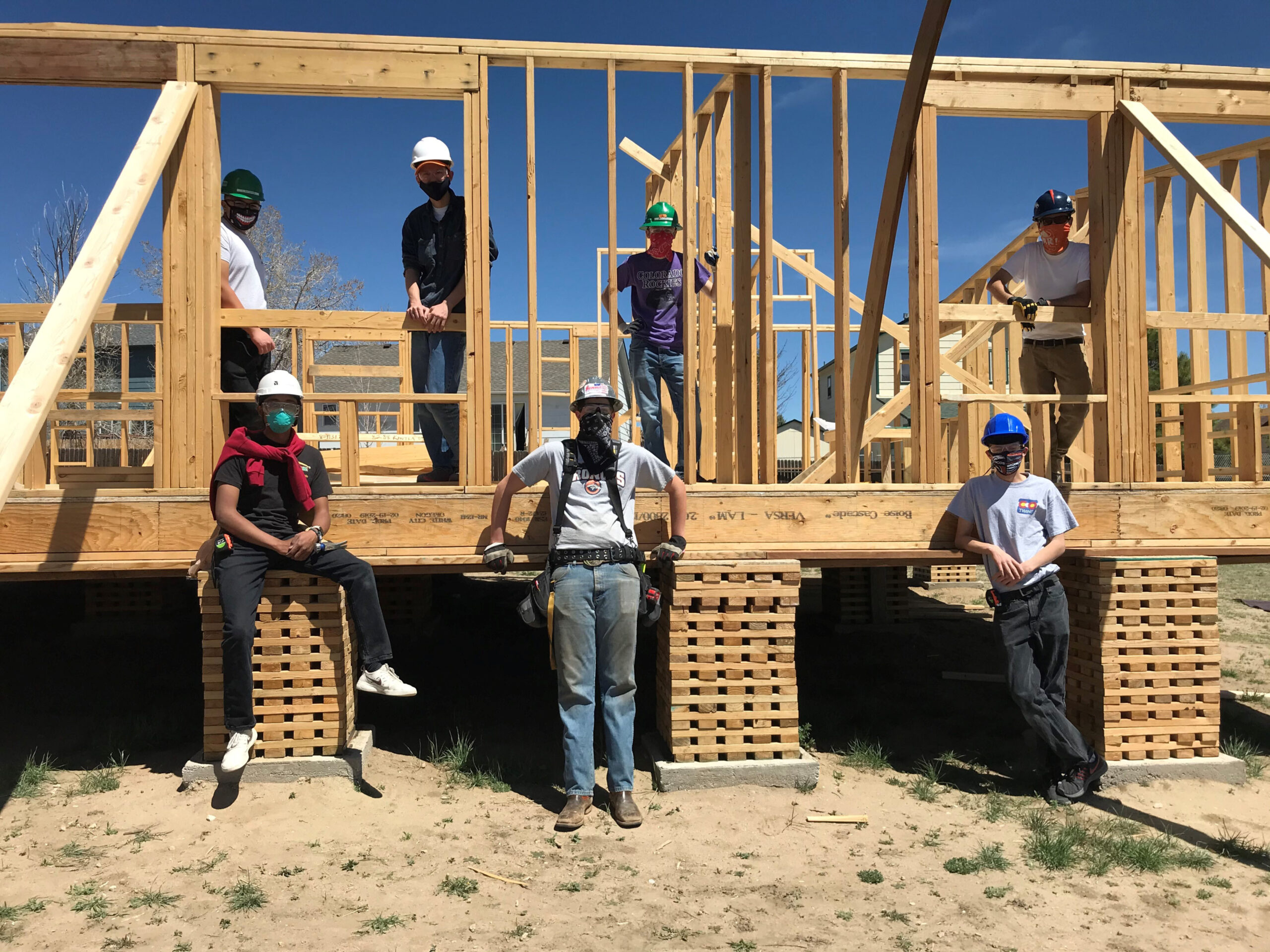 7 Careers in Construction Students standing on and in front of a frame of a house they built. All students wearing face masks.