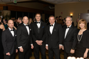 6 people posing for a photo at a black tie event