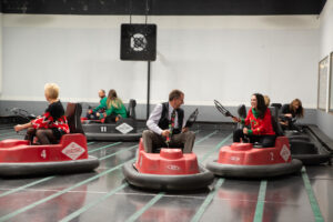 7 people playing whirly ball on bumper cars