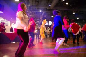 group of people dancing on the dance floor