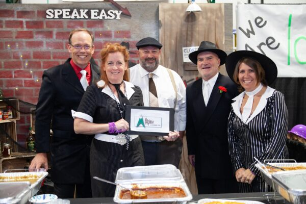 Five people posing for a photo in front of their booth at an event
