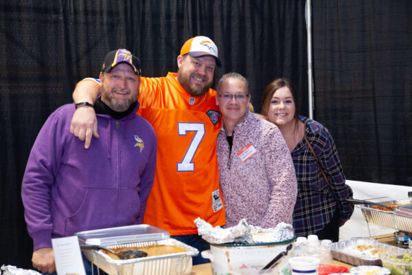 Four people posing for a photo at an event
