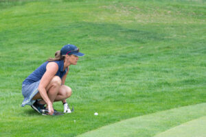 one person crouched lining up a putt on a golf course