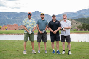 4 people posing for a picture on a golf course