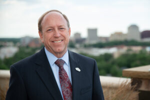individual photo of John Suthers with downtown Colorado springs in the background